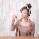 コップで水を飲む女性
