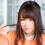 箸で寿司をつまみ見つめる女性
